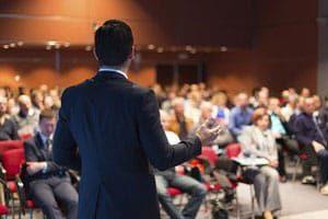 Photo d'un conférencier de dos devant son public